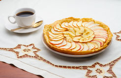 Golden Apple Tart and Coffee Cup. A tasty golden homemade apple tart and a cup of black coffee on an embroidered tablecloth Stock Photography
