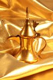 Golden arabic coffee / tea pot. In gold background Royalty Free Stock Photography