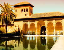 Golden Arabic palace, pool and palm. This post-islamic palace - part of Alhambra fortress (Granada, Spain) is now world known museum Stock Image