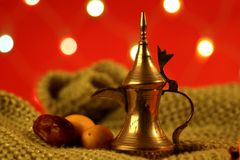 Golden arabic tea pot with dates. Golden arabic tea pot with red blurred lights in the background Stock Photo