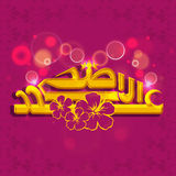 Golden Arabic text for Eid-Al-Adha celebration. Golden Arabic Islamic calligraphy of text Eid-Al-Adha with flowers on floral design decorated shiny background Stock Photos