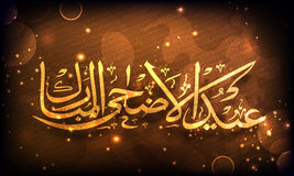 Golden Arabic text for Eid-Al-Adha celebration. Royalty Free Stock Image