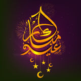 Golden Arabic Text for Eid Festival celebration. Golden Arabic Islamic Calligraphy of Text Eid Mubarak with hanging moons and stars on fireworks decorated Stock Photo