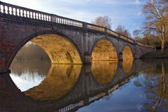 Golden Arches. Sunlit arches of a stone & brick bridge, reflecting in a calm lake Stock Photos