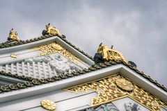 Golden architectural detail ornaments at Osaka Castle in Japan. Plant inspired golden ornaments at Osaka Castle Pagoda with white walls and specific green roof royalty free stock photos