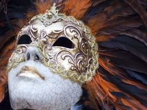 Golden artistic Venetian mask. Golden artistic mask with orange and black feathers Stock Photo