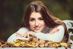 Golden autumn and garden. A portrait of a beautiful young woman sitting at a table covered with golden autumn leaves. Lifestyle, autumn fashion, beauty stock photography