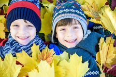 Golden Autumn, group of children lie on their backs in yellow leaves, Happy children in autumn park lying on leaves.  royalty free stock photography