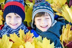 Golden Autumn, group of children lie on their backs in yellow leaves. Happy children in autumn park lying on leaves royalty free stock photography