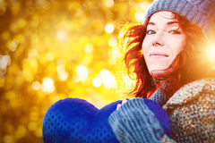 Golden autumn portrait of young pretty girl with blue heart in her hands Royalty Free Stock Images