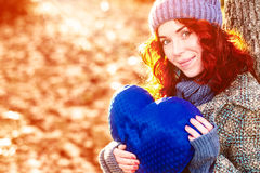 Golden autumn portrait of young pretty girl with blue heart in her hands Royalty Free Stock Photo