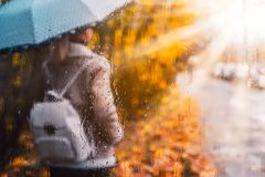 Golden autumn season. Watercolor like blurred blond girl with backpack and bright umbrella stands under rainy drops and stock image