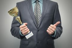 Golden award cup in the winner hands. royalty free stock image