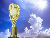 Golden award winning trophy on blue sky and sun background.  Stock Photos