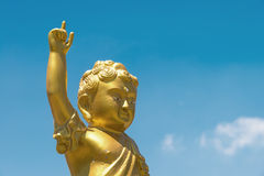 Golden baby Buddha statue raise arm and point forefinger up to b Stock Images