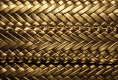 Golden  background with braided. Golden luxury background texture with a relief pattern Royalty Free Stock Photo