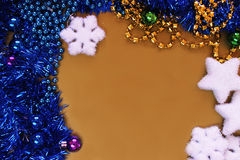 Golden background with Christmas balls and tinsel, beaded. Stock Photos
