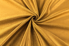 Golden background luxury cloth or wavy folds of grunge silk texture satin Stock Photography
