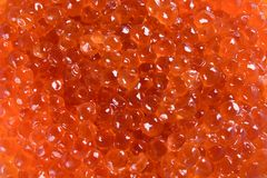 Golden background of scattered red caviar royalty free stock photography
