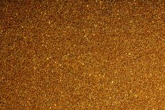 Golden background with sparkles texture of large resolution. Yellow shiny and iridescent sequins with lights and light background Stock Photo