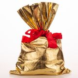 Golden bag of gifts isolated on a white background. Studio photography royalty free stock image