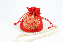 Golden bag and pearl necklace Stock Image