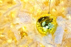 Golden Ball Bauble Reflecting Snow Flakes on Christmas tree. Golden Ball Bauble Reflecting Snow Flakes Decorated on Christmas tree Royalty Free Stock Photo