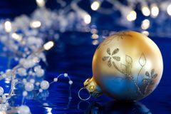 Golden ball with Christmas lights. Golden ball with Christmas pearl lights against blue background Royalty Free Stock Image