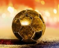 Golden ball on ground. Golden soccer ball on ground of football field stock images