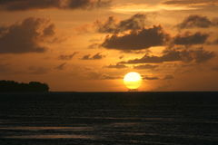 Golden ball. A huge golden ball sets in the horizon. Saipan, Northern Mariana Islands stock image