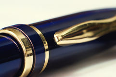 Golden ball pen latch. Gold-blue business pen latch closeup stock image