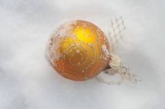 Golden ball on snow christmas Stock Photos