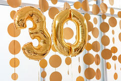 Golden balloons with ribbons - Number 30. Party decoration, anniversary sign for happy holiday, celebration, birthday. Carnival, new year. Metallic design Stock Photography