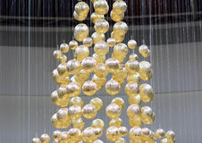 Golden balls on strings. This is the image of candy wrapped in gold, which hang on transparent filaments Stock Photos