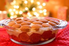 Golden banana pudding. Banana pudding with golden vanilla wafers on top in glass bowl in front of glowing Christmas tree with white shiny lights Stock Image