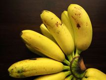 Golden bananas. A hand of golden bananas on wood table Stock Images