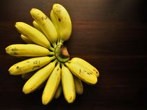 Golden bananas. A hand of golden bananas on wood table Royalty Free Stock Image