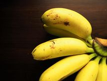 Golden bananas. A hand of golden bananas on wood table Royalty Free Stock Images