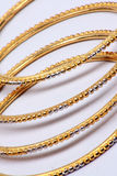 Golden Bangles. A pattern of beautiful gold bangles on a white fabric Stock Images
