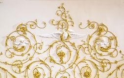 Golden baroque ornament. Vintage elegant golden baroque ornament on the wall royalty free stock photo