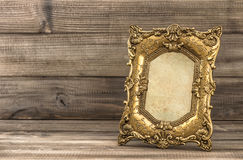 Golden baroque picture frame on wooden background Stock Photos