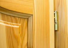 Golden barrel hinge on the wooden door Royalty Free Stock Photo