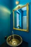 Golden basin in bathroom. Golden basin in new luxury blue bathroom royalty free stock photo