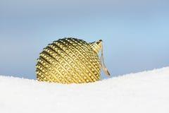 Golden bauble. Golden christmas ball in snow Stock Photos