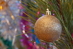Golden bauble on Christmas tree Royalty Free Stock Image