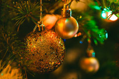 Golden bauble in Christmas tree surrounded by colorful lights Stock Photos