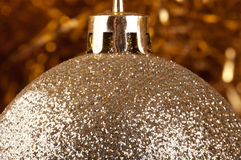 Golden bauble on a gold background. Royalty Free Stock Image