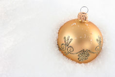 Golden bauble laying on snow Royalty Free Stock Photography