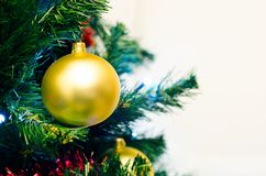 Golden bauble on xmas tree Stock Photo