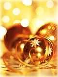 Golden baubles Christmas tree ornament. Winter holidays decoration, ornamental decorative toys over gold background with magic glowing blur bokeh lights Stock Photo